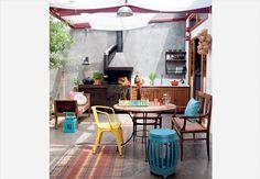 A cobertura de vidro laminado tem tecidos que suavizam a entrada de luz natural sobre o pátio, com churrasqueira de ferro esmaltado, mesa com cadeiras diferentes, garden seat e banco. Projeto LT Arquitetura