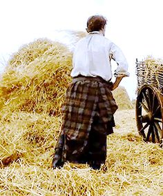 (gif)  James Alexander Malcolm Mackenzie Fraser looking wistfully in the distance as he labors over a bale of hay at Lallybroch. *gasms*