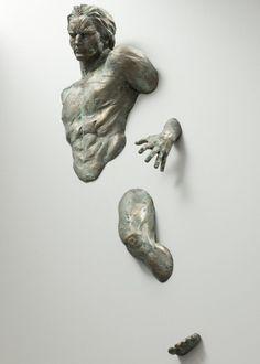 """Esta é uma das esculturas fantásticas do escultor italiano Matteo Pugliese, """"O homem atravessando paredes"""", feitas em bronze."""