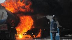 A fireman looks the other way as a fire burns in an oil tanker