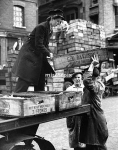 World War Two Home Front. A woman delivery boxes full of fish to traders in Billingsgate market, London September 1943
