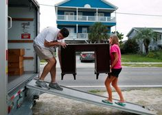 Dean Legge helps his sister‐law Josey Vereen remove furniture from the lower level of her beachfront home along in anticipation of Hurricane Matthew in Garden City Beach, SC, on Tuesday.