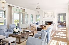Hamptons style living room with pale blue and white slip covered sofas. White walls, timber floors, pendant lighting and fireplace.