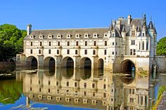 a castle atop a bridge on a river in France