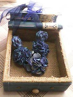 Caja de bambu azul, madera forrada con yute en su interior y exterior. Incluye collar de flores de tela.