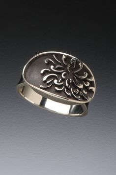 The chrysanthemum design on this ring was inspired by a textile pattern and the fine detail was achieved using CAD CAM. The recessed areas are