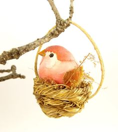 Sweet little Christmas tree ornament of a rose colored bird with tree bark wings and tail sitting in a nest. This would be perfect on your
