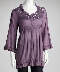 """Delicate and drapey, this tunic invokes the elegance of ages past. Exquisite crochet lace opens the neck and back, while long sleeves end in a flourish of frills."""
