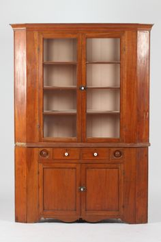 """LARGE AMERICAN MAPLE CORNER  CABINET; EASTERN PENNSYLVANIA MADE, 1st Half 19th Century. In two parts. Upper case having molded cornice over two glazed door panels, opening to three shelves. Lower cabinet having two short drawers over two door panels opening to one shelf. - 82 5/8"""" high x 55 7/8"""" wide x 34 1/2"""" deep. #SloansAndKenyon, #Furniture"""