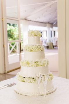 Elegant four-tiered cake with white hydrangeas: http://www.stylemepretty.com/little-black-book-blog/2015/09/03/classic-southern-cheekwood-botanical-gardens-wedding/   Photography: Bamber Photography - http://bamberphotography.com/