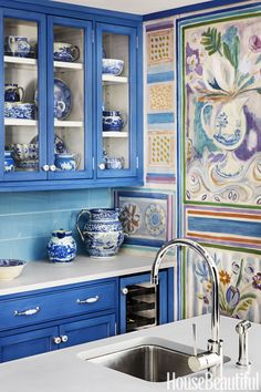 "Matching China China The custom hue sets off a blue-and-white china collection, and a decorative painting by Osmundo Studio hides the pantry door. On the island, Kohler's prep sink is paired with Rohl's Modern Architectural faucet. ""A second sink is always a good idea."""
