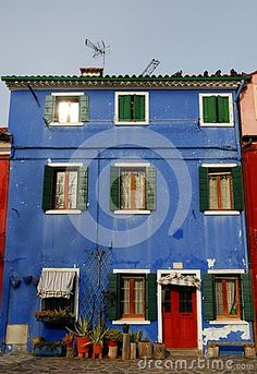 Photo made in the island of Burano in Venice in Italy. The picture shows the front of a single house of a deep blue color and very particular that seems to fade the blue sky. In front of the house and next to the front door you see some pots with succulents.