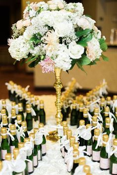 Wedding favor idea - mini bottles of champagne used as escort cards and wedding favors .