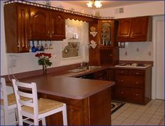 Booth Construction, Inc. - Kitchens & BathsTraditional maple cabinet with a cherry finish and raised cathedral doors. This kitchen features a custom range hood and beautiful corner cabinet with appliance garage.  Merlot Terra laminate countertop adds the finishing touch to this Cape Cod kitchen.