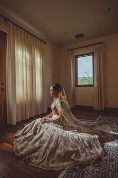 Bride sitting with dress layed out (shot from side & above) Sort of dramatic.
