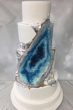 Silver accents and gradients of deep blue candy crystals to give the appearance of really gazing into cracked rock on this geode wedding cake.