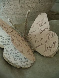 paper butterfly. Could be made with photos of bride and groom as favors. Or, could be made with family stats or even use old xmas cards as a reuse project