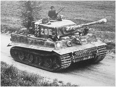 A Tiger 1 marked as number 205 is on the march with it's commander out of his hatch monitoring the area.