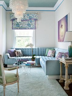 Dreamy Color Scheme Pastel blues featured on various surfaces throughout this living room play nicely with soft lavender accessories. Various textures, from the grass-cloth-covered celing to the tufted sofa and fluffy area rug, add interest to the matching blue tones. Lavender accents also break up the tone-on-tone scheme but don't overpower the room's calming aesthetic.