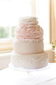 So pretty! Layered and textured blush pink wedding cake with floral ruffles and polka dot accent