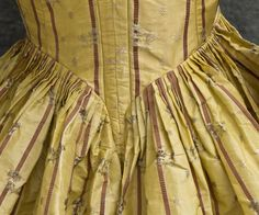 "Detail of back of a French brocaded silk taffeta open robe, 1780s. ""Silk taffeta with purple rib weave stripes and small ivory brocaded flowers. The neckline, front, and sleeves are edged with pleated ivory ribbon. The charming compères are decorated with appliqués of cut-out stripes and pleated ribbon"". Vintage Textile. See gown here: http://www.pinterest.com/pin/278589926923030159/"