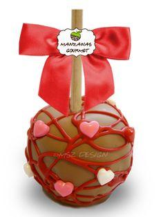 Manzana envuelta de caramelo con capa de chocolate de leche, decorada con tiras de chocolate color rojo y corazones de azúcar.