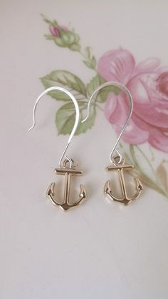 Tiny silver anchors dangle from silver ear wires.*Earrings measure 1.5 inches long, which includes the length of the ear wire.