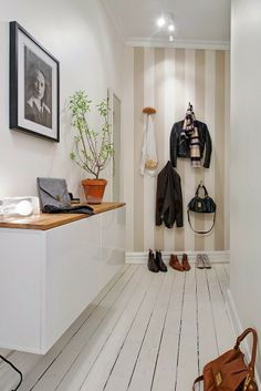 Striped wall in entryway with floating sideboard