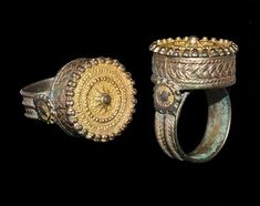 BYZANTINE GILT FINGER RING 14th-15th century AD A silver-gilt finger ring comprising a ribbed hoop with herringbone ornament to the outer face, a rosette plaque to each shoulder, drum-shaped bezel with ring-chain design to the sidewall, faux-granulation to the rim and upper face.