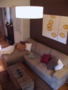 Earthy tones in a modern living room - L-shaped couch - artwork winks at mid-century modern.