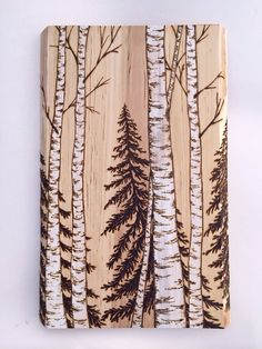 These birch and spruce trees have been burned into a slab of birch wood which has been planed, sanded, and rounded. It has the burnings coming around the corners to create a more wider-looking and interesting landscape. It measures 16 inches long by 10 inches wide. Its thickness is