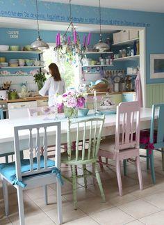 Keittiön suuren pöydän äärellä on tilaa perheen lapsille ja lapsenlapsille. Vanhat tuolit ovat Karinin isoisän suunnittelemia ja kirpputorilöytöjä. Karin maalasi tuolit eri väreillä, kuten keittiön alakaappien ovetkin.