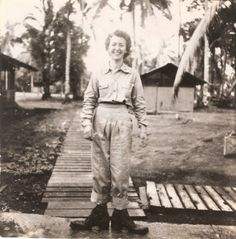 "Nedra Dawson Patrick on the Philippine island of Leyte during her service as an Army nurse during World War II. Her family writes that this photo of Patrick in her ""work uniform"" was taken by another nurse just after arrival at the jungle hospital where she worked. Her shoes had been stolen, and the only footwear available on the island was a pair of size 13 boots (to go along with the too-long pants)."