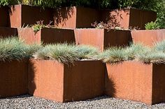 The simple extrusion of a pattern of grids to form a structure. Festuca glauca in corten steel raised beds