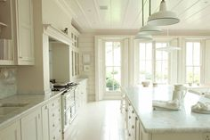 White country kitchen with long dinng table and glass wall cabinets