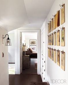 Clip boards are used to display a collection of sketches in this hallway. {seen in elle decor}