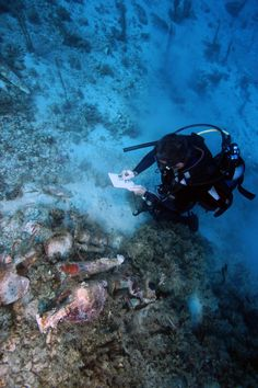 An underwater archaeologist takes notes on ancient jars found in a shipwreck. (Vasilis Mentogianis)