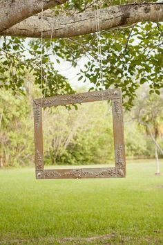 hang an empty picture frame from a tree branch at a rustic wedding reception / http://www.himisspuff.com/country-rustic-wedding-ideas/8/