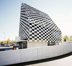 A chequerboard of solid and void cloaks the tapered glass walls of this bank