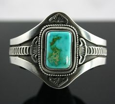 Sammie Kescoli Begay Royston Turquoise Ingot Bracelet | eBay    This simple yet dazzling bracelet made by Navajo artist, Sammie Kescoli Begay, is set with beautiful Royston turquoise from Nevada. The cabochon contains hues of both blue and green with tan matrix and is encircled with fine hand woven wire and beads. It also includes two arrowhead shaped designs and two fans. The band of the piece features twenty eight crescent shape stamps on either side all brought out with dark oxidation…