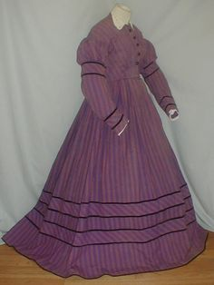 """Charming 1860's Dark Mauve Pink Stripe Challis Dress   eBay seller fiddybee; puffed top on sleeves, black velvet trim; original white eyelet collar; bodice lined with cotton & has front hook & eye closure; black jet buttons are decorative; piping at neck, armscyes & waist; skirt unlined except wide band of cotton at hem; no underarm discoloration; bust: 34""""; waist: 26""""; skirt length: 43""""; hem width: 126"""""""