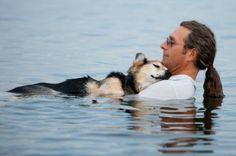 En man vaggar sin 19-åriga, artritsjuka hund till sömns i vattnet.