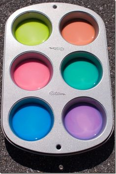 Sidewalk chalk paint is so much cooler than regular old sidewalk chalk! And it's crazy easy to make! It's simply 1 part cornstarch to 1 part water. I made two muffin tins of paint and used 1-1/2 cups cornstarch and 1-1/2 cups water. Once it was all mixed up, I divided it among the 12 muffin cups, and added two drops of food coloring to each muffin cup