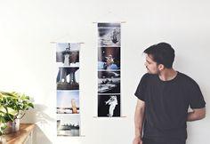 man standing next to giant photo strips