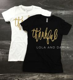 Thankful womens t shirt Thankful is printed in gorgeous golden sparkle! Pictures do not do the sparkle justice! THESE DO RUN A SIZE SMALL! If you normally wear an x small, order a small! They are super comfy and the sparkle is amazing! Available on black or white t shirt. 60% ring-spun combed cotton/40% polyester  Production time is approximately 3-7 business days.  Machine wash cold inside out and tumble dry low.  Thanks for sparkling with Lola and Darla!  Please note: Because our items are…