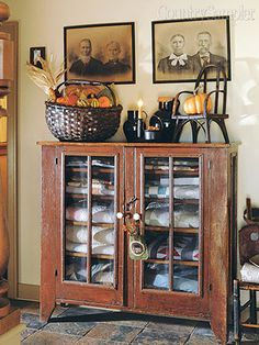 Similarly, stuff an oversize basket with fall fare, placing a pumpkin in the back to help hold smaller items in place. In this entryway vignette in Kathy and Todd Daggett Primitive Living Room, Primitive Furniture, Primitive Fall, Primitive Decor, Country Primitive, Comfy Cozy Home, Country Sampler Magazine, Quilt Display, Kitchen Buffet