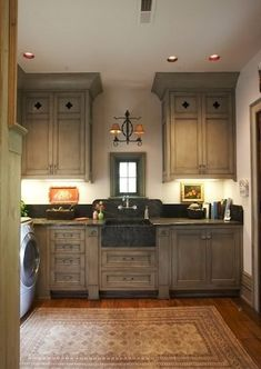 Lovely laundry room! Check out the quatrefoil design on the cabinets and farmhouse sink.