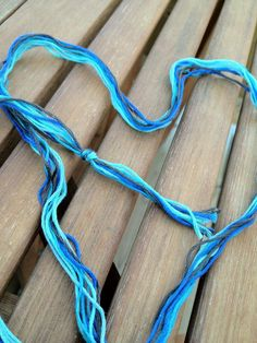 Bunch your strings together and tie a knot at one end. You could also double the length of the strings and fold in half, tying in a loop knot instead. So you would have 3 strings, 1 of each color.
