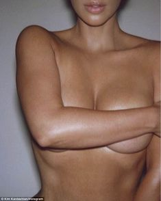 Flashing the flesh: Kim Kardashian shared a saucy topless snap on Tuesday showing her topless as she plugged her new perfume
