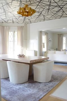Under a ceiling clad in Kelly Wearstler Channels Wallpaper, this chic contemporary dining room features a gold chandelier hung over an oak dining table surrounded by white barrel back dining chairs placed on a purple rug, as natural light streams in from a window dressed in cream curtains.